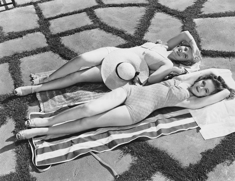 Hoge hoekmening die van twee jonge vrouwen op een handdoek in de zon liggen (Alle afgeschilderde personen leven niet langer en ge stock foto