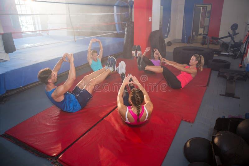 Hoge hoekmening van atleten die terwijl het liggen op matten uitoefenen stock fotografie