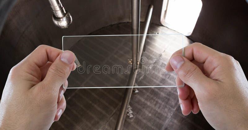 Hoge hoekmening van bebouwde handen die materiaal fotograferen bij brouwerij stock afbeeldingen