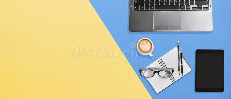 Hoge hoekmening van bureau kleurrijk bureau met exemplaarruimte, Laptop, notitieboekje, tablet en koffie stock foto