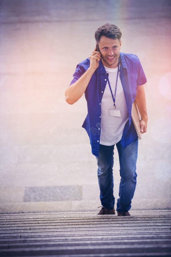 Hoge hoekmening van de knappe mens die op treden lopen terwijl het spreken op mobiele telefoon stock foto's