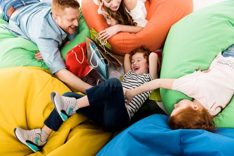 hoge hoekmening van gelukkige familie met het winkelen zakken die pret op boon hebben stock afbeelding