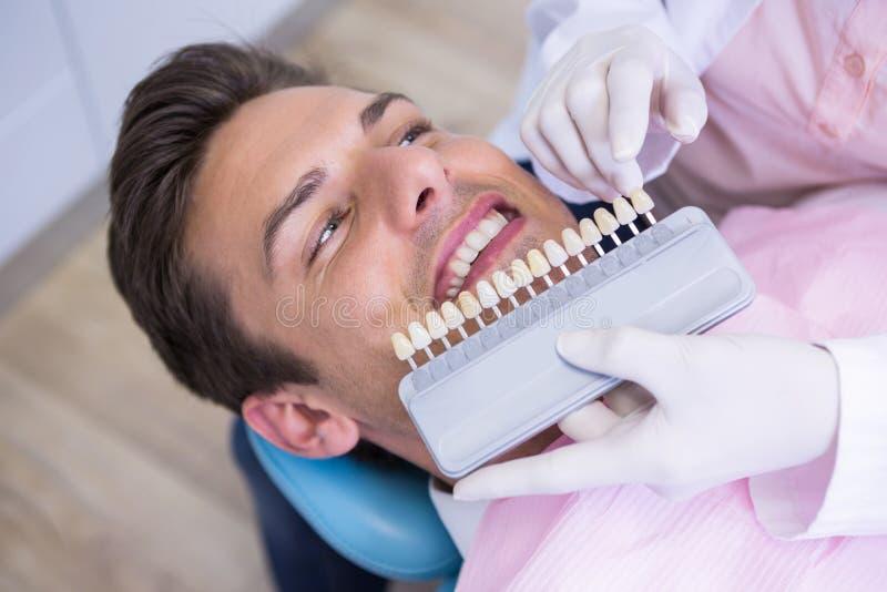 Hoge hoekmening van het materiaal van de tandartsholding terwijl het onderzoeken van patiënt royalty-vrije stock afbeelding