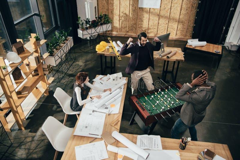 hoge hoekmening van jonge architecten die lijstvoetbal spelen stock foto's