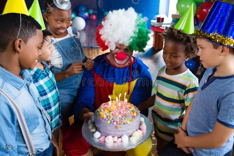 Hoge hoekmening van kinderen met clown status door cake royalty-vrije stock foto's