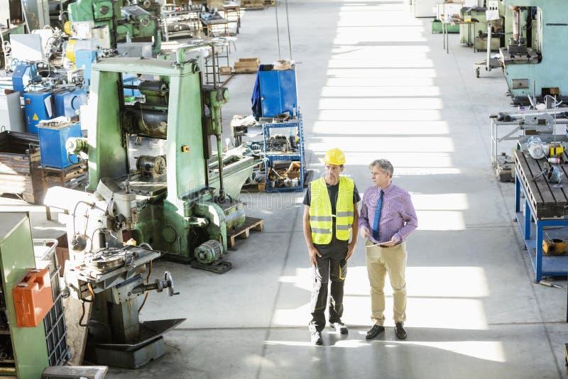 Hoge hoekmening van mannelijke supervisor en handarbeider die bespreking in de metaalindustrie hebben stock afbeelding