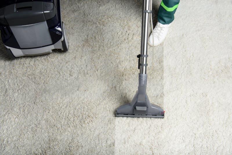 hoge hoekmening van persoon die wit tapijt met professioneel vacuüm schoonmaken stock foto's