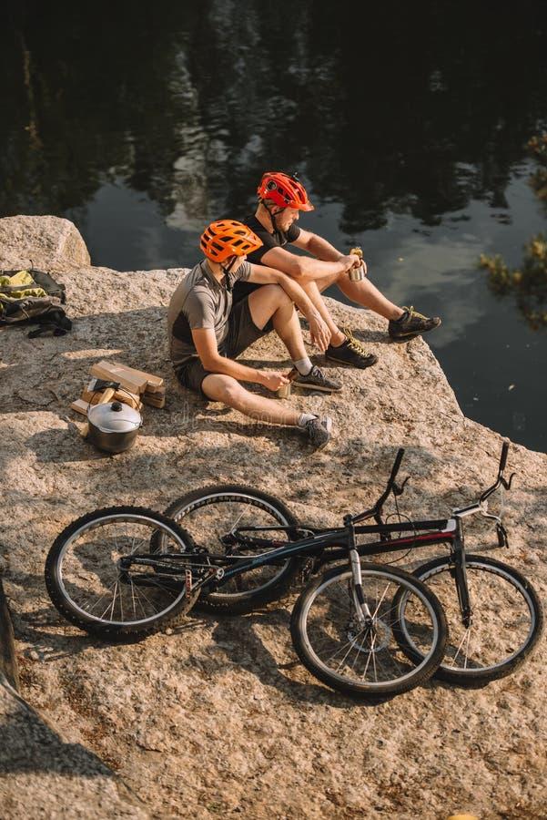 hoge hoekmening van proeffietsers die dichtbij van de logboekenketel en berg cycli op rotsachtige klip rusten royalty-vrije stock afbeelding