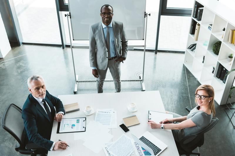 hoge hoekmening van professionele multi-etnische bedrijfsmensen die bij camera tijdens vergadering glimlachen stock afbeelding