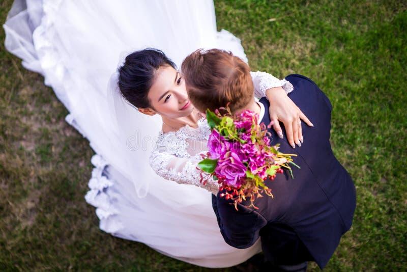 Hoge hoekmening van romantisch huwelijkspaar op grasrijk gebied stock foto's