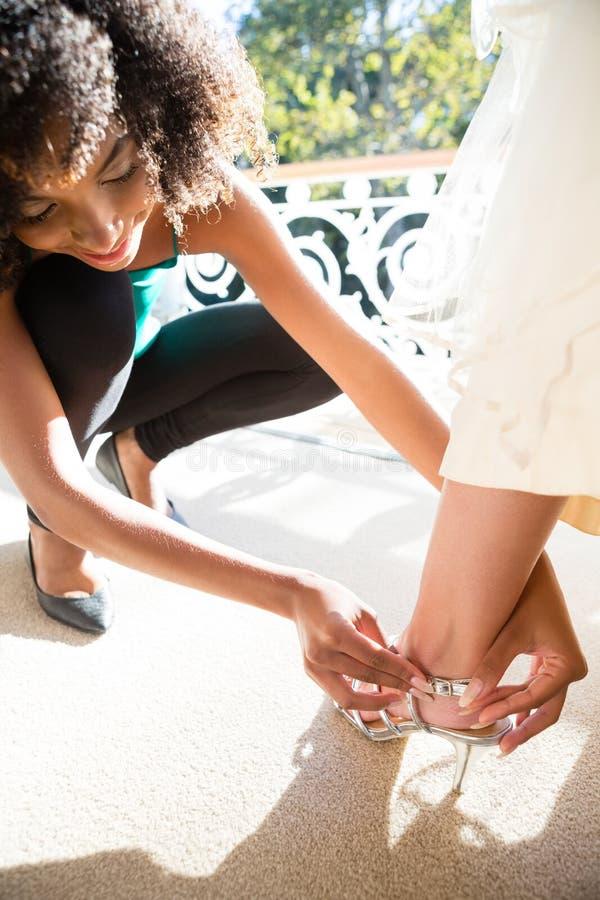 Hoge hoekmening van schoonheidsspecialist die op sandals aan bruid zetten stock afbeelding