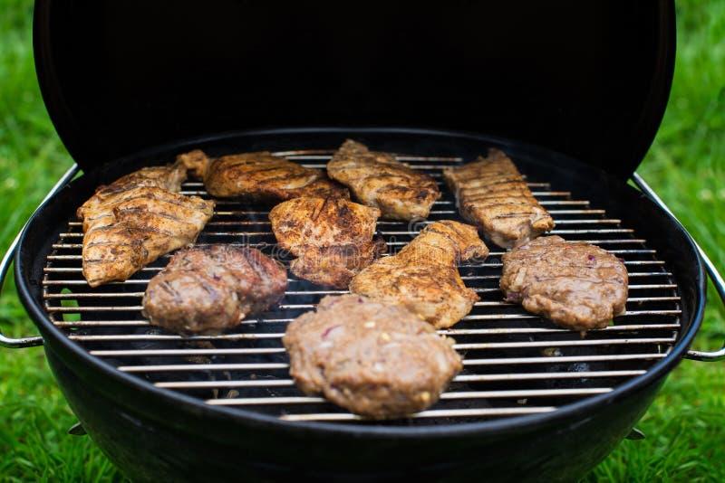 Hoge hoekmening van succulente lapjes vlees en burgers die op een barbecue over de hete steenkolen op een groen gazon in openluch royalty-vrije stock foto's