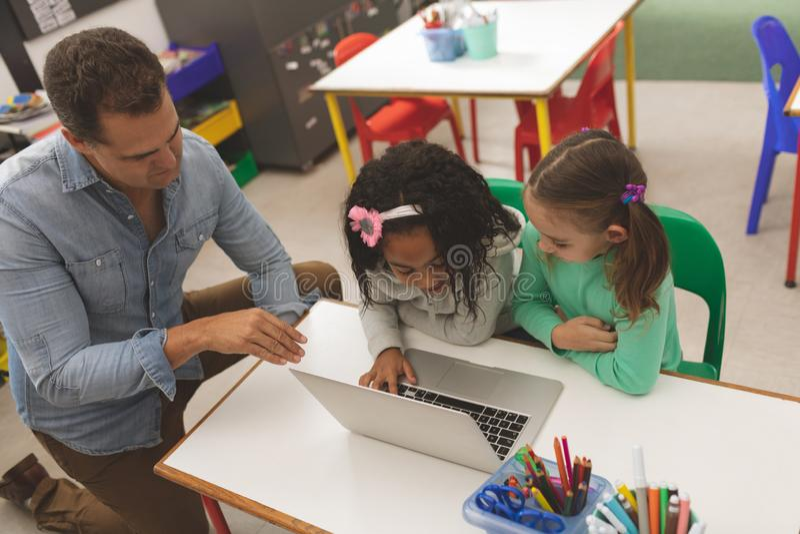 Hoge hoekmening van twee schoolmeisjes die aan één laptop werken terwijl het hun leraarsonderwijs hen hoe te u stock afbeeldingen