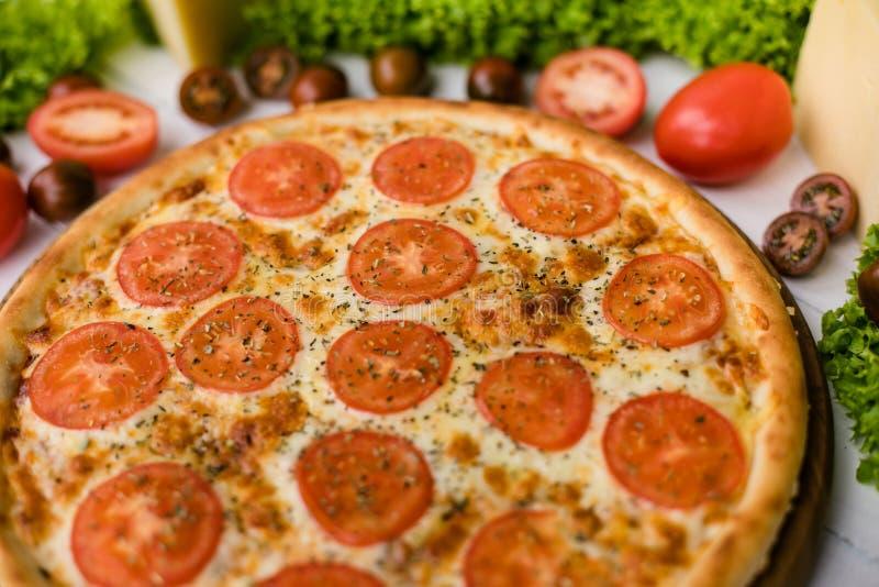 Hoge hoekmening van verse pizza op witte houten die lijst door salade, groenten en kaas wordt omringd royalty-vrije stock foto