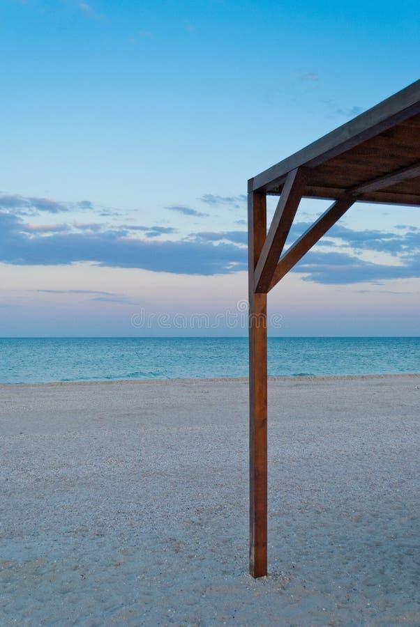 Hoge houten vroeg verlaten luifel afbaardende as, strand in de ochtend stock afbeeldingen