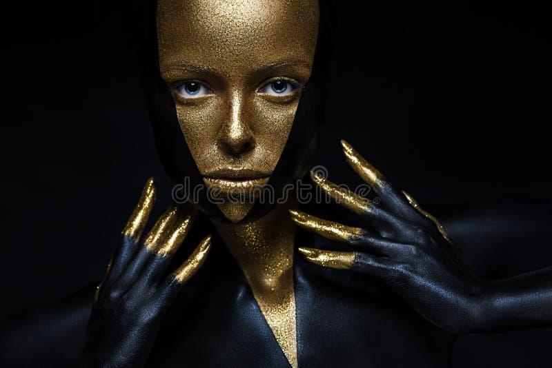Hoge mannequin met zwart en gouden leer, gouden vingers Geïsoleerd op zwart achtergrondschoonheids vrouwelijk gezicht, stock foto