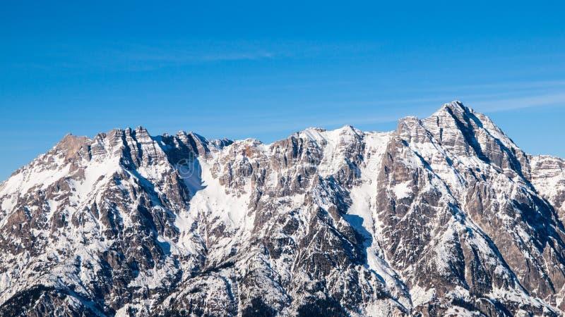 Hoge rotsachtige sneeuwpiek op zonnige de winterdag met blauwe hemel Alpiene bergrand stock foto's
