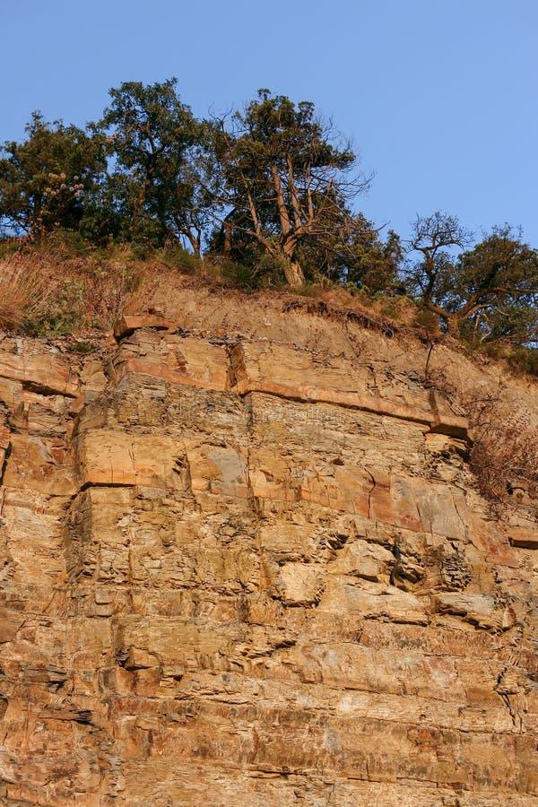 Hoge rufous rots van zandsteen en jeneverbessenbomen die op zijn bovenkant groeien royalty-vrije stock foto's