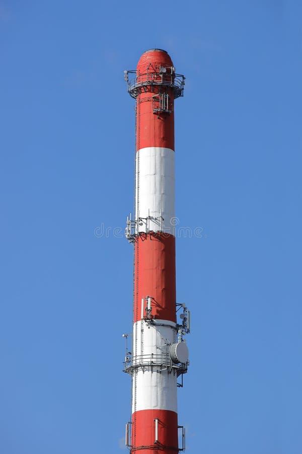 Hoge schoorsteen bij de installatie in rood-witte kleur met materiaal voor het uitzenden radio Het installeren van een cellulaire royalty-vrije stock foto