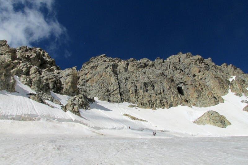 Hoge sneeuw en rotsachtige bergketen, kleine mensencijfers op sneeuw stock foto's