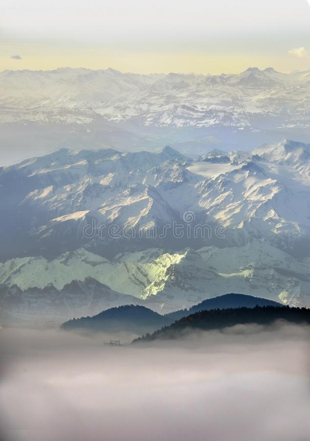 Hoge sneeuwbergen boven wolken royalty-vrije stock afbeelding