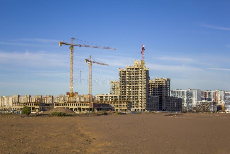 Hoge torenkranen dichtbij de betonconstructies in aanbouw van wolkenkrabbers tegen de achtergrond van moderne high-rise stock foto's