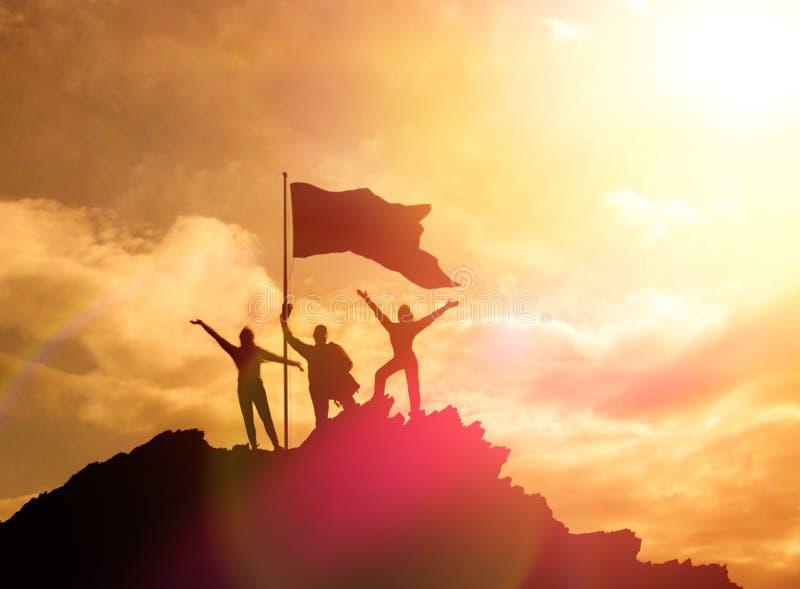 Hoge uitvoerder, silhouetten van drie mensen die bovenop een berg houden om hun handen omhoog op te heffen stock fotografie