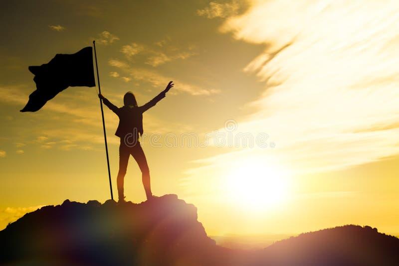 Hoge voltooiing, silhouetten van het meisje, vlag van overwinning op de bovenkant van de berg, handen omhoog stock fotografie