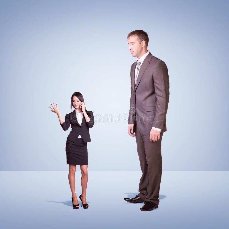 Hoge zakenman die neer weinig vrouw bekijken royalty-vrije stock afbeeldingen
