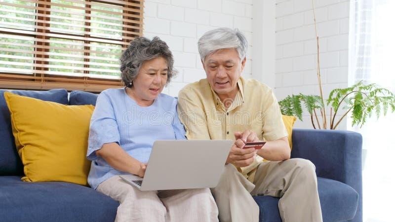 Hoger Aziatisch paar die online door laptop computer en creditcard thuis woonkamer winkelen, de technologie van Pensioneringsmens stock foto's