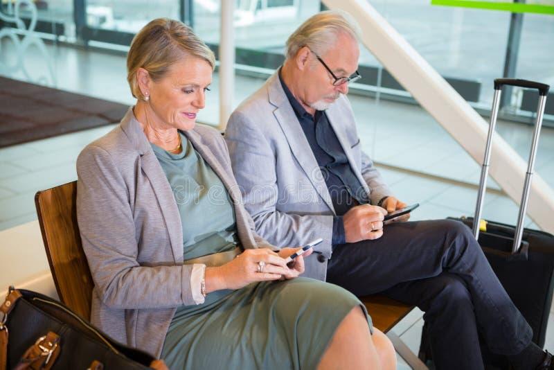 Hoger Bedrijfspaar die Mobiele Telefoons in Luchthavenhal met behulp van royalty-vrije stock foto