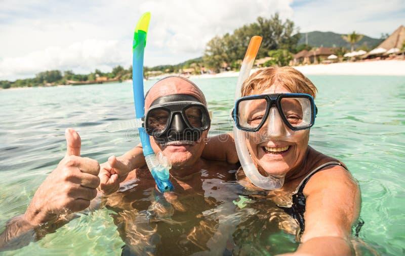 Hoger gelukkig paar die selfie met scuba-uitrustings snorkelende maskers nemen stock foto