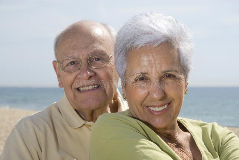 Hoger glimlachend paar bij het strand stock afbeelding