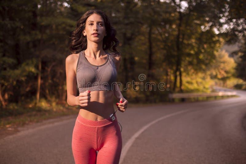 Hoger lichaamsschot, één jonge vrouw, lopende jogging, sportslijtage, s stock foto