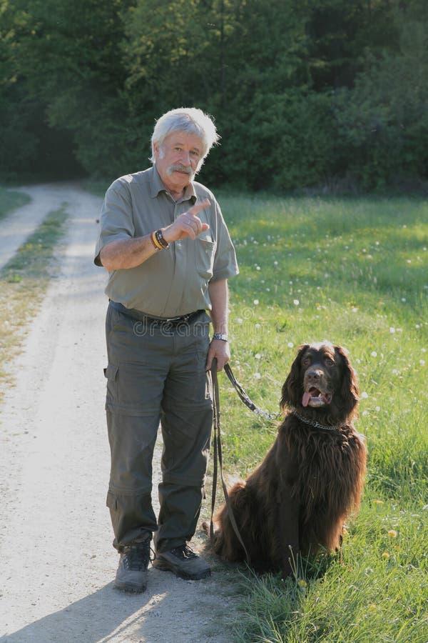 Hoger mannetje met hond stock afbeeldingen
