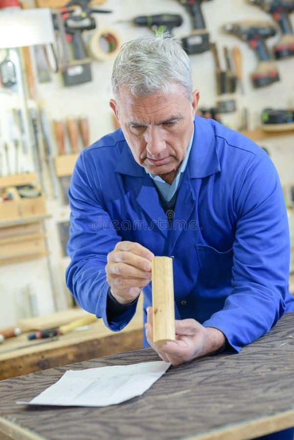 Hoger mens het inspecteren stukhout in workshop stock afbeeldingen