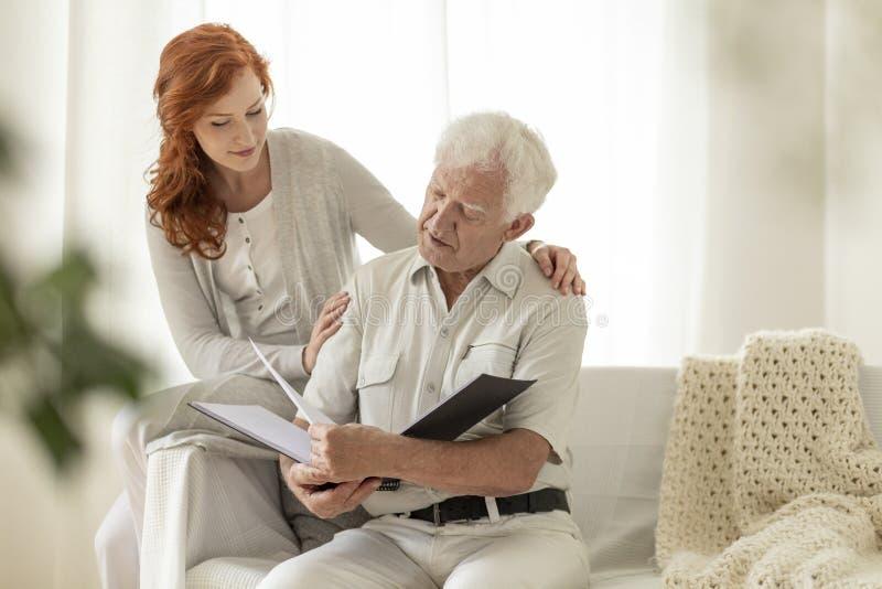 Hoger mens het letten op fotoalbum tijdens bezoek van kleindochter bij stock foto