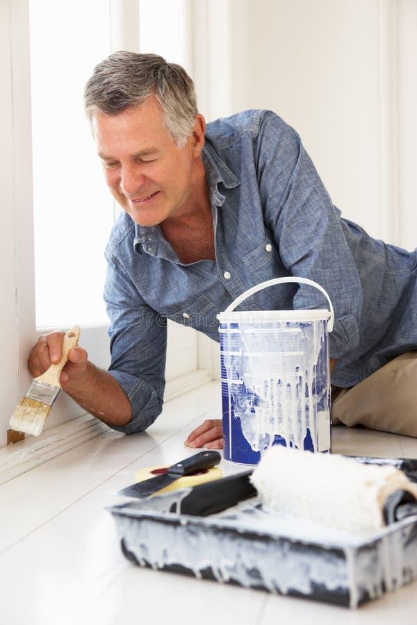 Hoger mens het schilderen huis stock fotografie