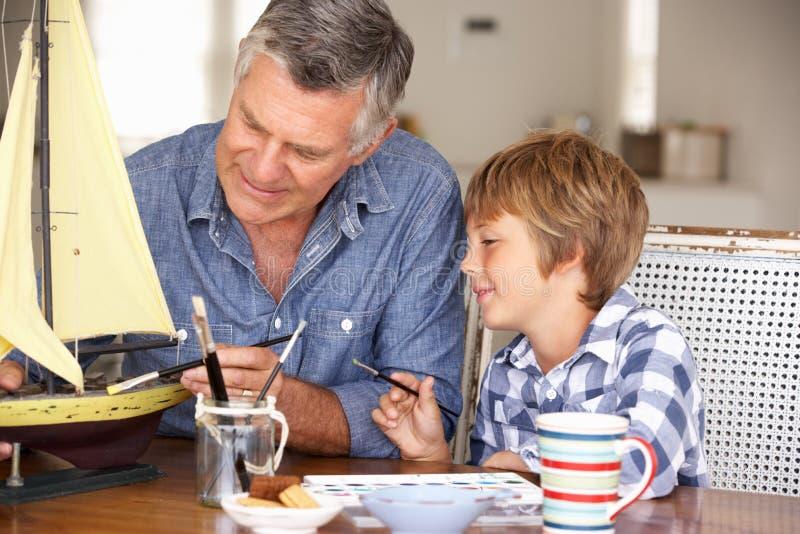 Hoger mens het schilderen model met kleinzoon stock foto's