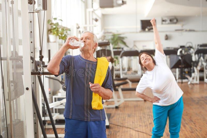 Hoger mensen drinkwater na training royalty-vrije stock afbeelding
