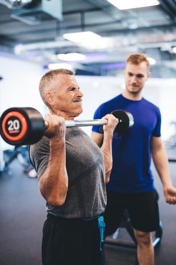Hoger mensengewichtheffen, bijgestaan door persoonlijke trainer royalty-vrije stock foto's