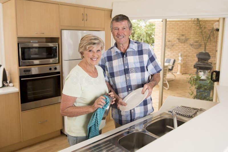 Hoger mooi middenleeftijdspaar rond 70 jaar oude het glimlachen gelukkige thuis keuken die de schotels wassen die samen zoet kijk stock foto