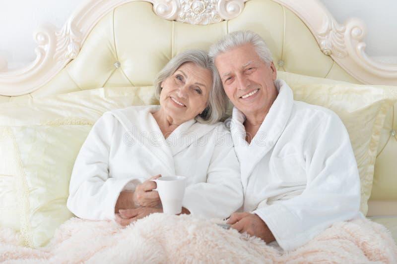 Hoger paar in bed met thee royalty-vrije stock foto