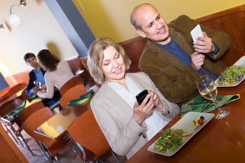 Hoger paar bezig met telefoons op datum in koffie royalty-vrije stock afbeelding