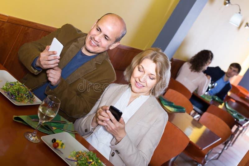 Hoger paar bezig met telefoons op datum in koffie stock foto's