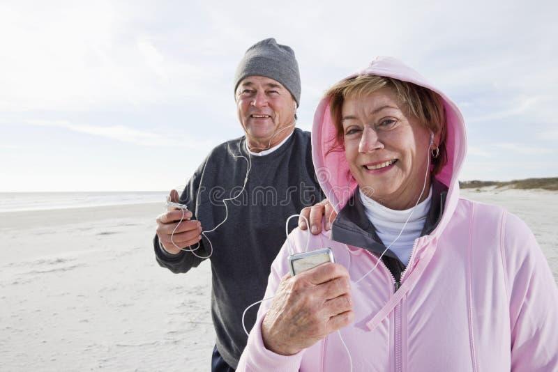 Hoger paar dat aan muziek op MP3 speler luistert stock foto's