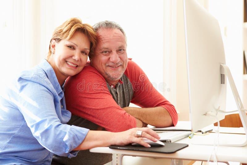 Hoger paar dat computer thuis met behulp van stock afbeelding