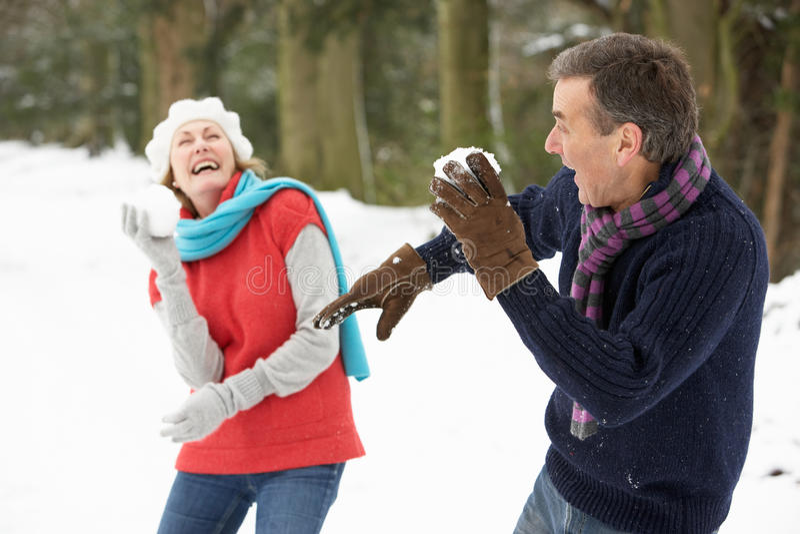Hoger Paar dat de Strijd van de Sneeuwbal in Sneeuw heeft royalty-vrije stock afbeeldingen