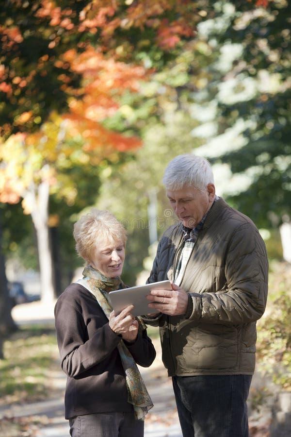 Hoger Paar dat digitale tablet bekijkt stock foto