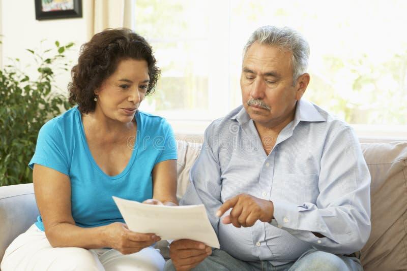 Hoger Paar dat Financieel Document thuis bestudeert stock afbeeldingen